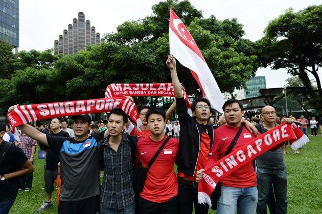 SINGAPORE - FEBRUARY 16: People in Singaporean scarves as they sing the National Anthem during the protest against the government's White Paper on Population at Speakers' Corner at Hong Lim Park on February 16, 2013 in Singapore.