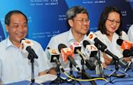 Opposition Workers' Party's Png Eng Huat (C) who won the Hougang by-election smiles along with the party's Secretary-General Low Thia Khiang (L) and chairman Sylvia Lim Swee Lian (R) during a press conference in Singapore