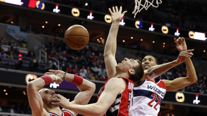 Washington Wizards center Marcin Gortat (4), from Poland, Toronto Raptors forward Tyler Hansbrough (50) and forward Otto Porter Jr. (22) go for the rebound in the first half of Game 4 in an NBA basketball first-round playoff series, Sunday, April 26, 2015, in Washington. (AP Photo/Alex Brandon)