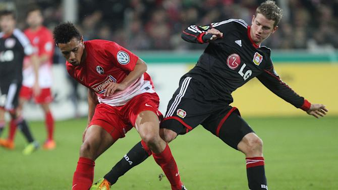 Freiburg's Admir Mehmedi of Switzerland, left, and Leverkusen's Lars Bender challenge for the ball during a round of 16 German soccer cup match between SC Freiburg and Bayer Leverkusen in Freiburg, Germany, Wednesday Dec. 4, 2013
