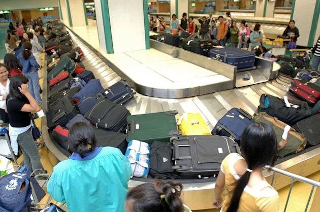 This file photo shows a group of Filipino domestic workers collecting their luggage from a carousel at Manila airport, on August 15, 2006. The Philippines is to resume sending workers to Israel as the situation there returns to normal after last month's violence, the foreign department said on Friday