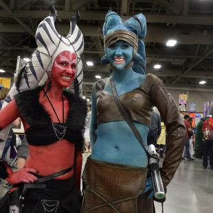 "Hope Twede, left as a Sith, and Jessica Johnson, as Jedi ""Ayala Secura"" pose for a photo on the floor at the opening day of Salt Lake Comic Con, Thursday, April 17, 2014, in Salt Lake City, Utah. (AP Photo/The Salt Lake Tribune, Scott Sommerdorf)"