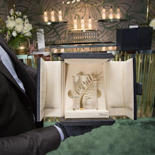 A person poses for a photograph with a box containing the Palme d'Or award, which will be presented on Sunday, at the 68th international film festival, Cannes, southern France, Saturday, May 23, 2015. (Photo by Vianney Le Caer/Invision/AP)