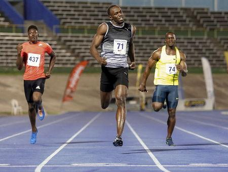 Bolt crosses the finish line first to win his first 200m race for the season with a time of 20.20 seconds next to Francis and Carter during the UTECH Classic 2015 at the National Stadium in Kingston