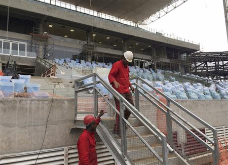 A worker walks down a stair in the construction of the Arena Pantanal soccer stadium in Cuiaba