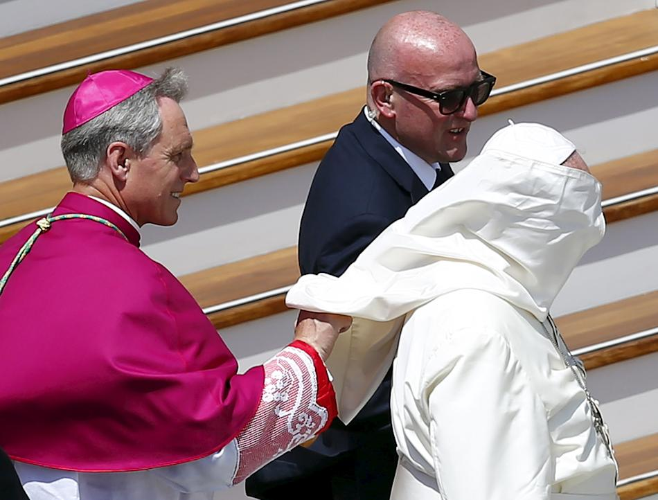 Archbishop Georg Ganswein helps Pope Francis with his mantle as a gust of wind blows at the end of the ceremony for the canonisation of four nuns at Saint Peter's square in the Vatican City