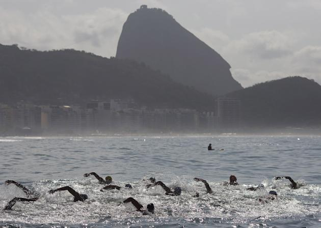 FILE -In this Aug. 22, 2015 file photo, backdropped by Sugar Loaf Mountain, athletes compete in the men's marathon swimming test event, ahead of the Rio 2016 Olympic Games, off Copacabana Beach, R