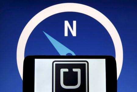 Photo illustration of Uber logo on a smartphone in front of a displayed logo of HERE, Nokia Oyj's map business, in Zenica