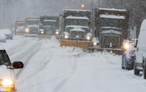 Snowplows clear the snow covered streets on March 5, …