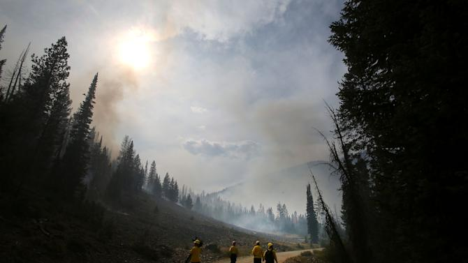 "FILE - In this Aug. 19, 2013 file photo, members of the media wa;l through part of the 104,457 acres Beaver Creek Fire in the Baker Creek area north of Ketchum, Idaho. With its mountain backdrop, Sun Valley is normally a playground for the rich, the famous, for super-fit pursuers of outdoor sports or the Big Wood River's feisty brook trout. To many, it's heaven. But the fire known as ""the Beast"" has raised hell with the sun-basking, fun-loving lifestyle. (AP Photo/Times-News, Ashley Smith, File) MANDATORY CREDIT"