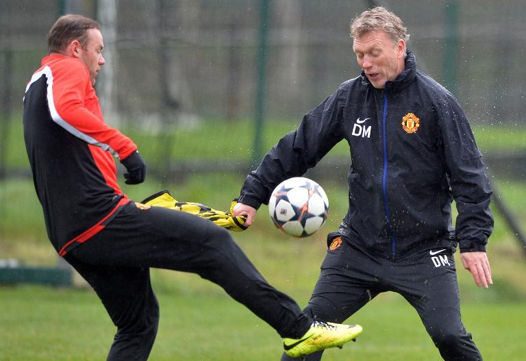 Manchester United's then manager David Moyes (R) takes part in a training session with striker Wayne Rooney at their Carrington training complex in Manchester, northwest England, on March 18, 2014