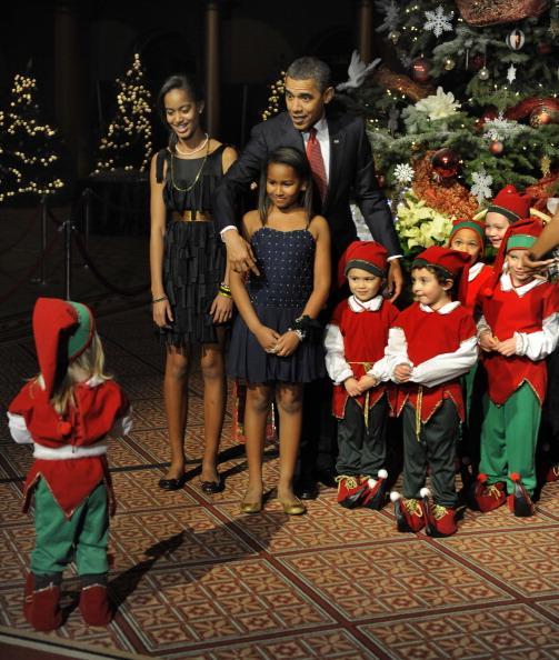 US President Barack Obama gestures to a wayward child to join the group of other children also dressed in Christmas elves costumes for a photo at a Christmas In Washington celebration at the Building