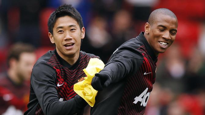 Manchester United's Kagawa jokes with Young on the pitch before their English Premier League soccer match against Liverpool at Old Trafford in Manchester