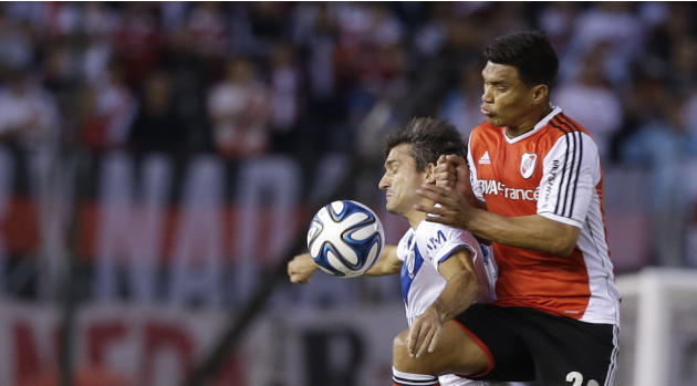 Velez Sarsfield's Emiliano Papa, left, fights for the ball with River Plate's Teofilo Gutierrez during an Argentine league soccer match in Buenos Aires, Argentina, Sunday, April 20, 2014