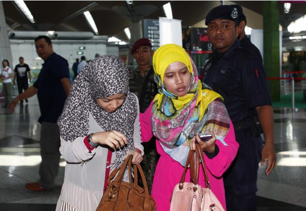 Family members of those onboard the missing Malaysia Airlines flight walk into the waiting area at Kuala Lumpur International Airport