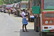 A truck driver brushes his teeth next to his parked truck while waiting to get his loads cleared to cross a checkpoint at the Commercial Taxes Department check post at Walayar in Palakkad district in Kerala, September 5, 2015. REUTERS/Sivaram V/Files