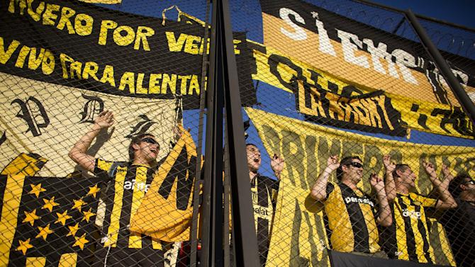 Uruguay's Penarol fans cheer for their team before the start of a Copa Libertadores soccer match against Argentina's Arsenal in Buenos Aires, Argentina,Thursday, March 13, 2014