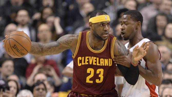 Cleveland Cavaliers' LeBron James (23) controls the ball as Toronto Raptors' Terrence Ross defends during the first half of an NBA basketball game Wednesday, March 4, 2015, in Toronto. (AP Photo/The Canadian Press, Frank Gunn)