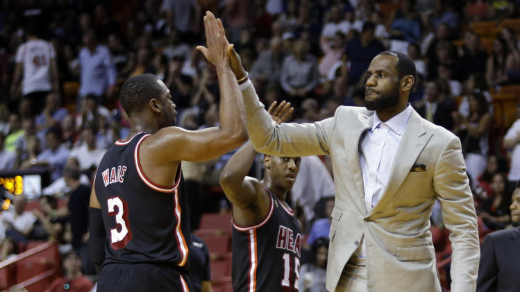 Miami Heat's LeBron James, right, high-fives Dwyane Wade (3) during a time out in the second half of an NBA basketball game against the Chicago Bulls, Sunday, Feb. 23, 2014, in Miami. The Heat defeated the Bulls 93-79. (AP Photo/Lynne Sladky)