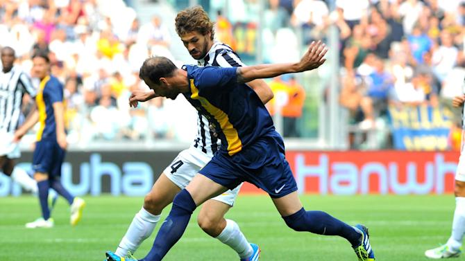 Juventus forward Fernando Llorente, of Spain, challenges for the ball with Hellas Verona defender Evangelos Moras, of Greece, during a Serie A soccer match between Juventus and Hellas Verona at the Juventus stadium, in Turin, Italy, Sunday, Sept. 22,  2013