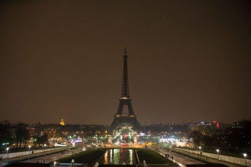 The Eiffel Tower is seen while submerging into darkness as part of Earth Hour on March 23, 2013 in Paris