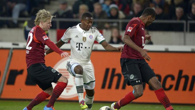 Bayern Munich's Alaba is challenged by Hanover 96's Rajtoral and Marcelo during the German Bundesliga first division soccer match in Hanover