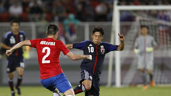 Serbia's Antonio Rukavina, left, challenges for the ball with Japan's Shinji Kagawa during their international friendly soccer match at Karadjordje stadium in Novi Sad, Serbia, Friday, Oct. 11, 2013