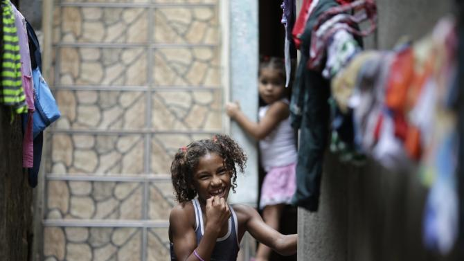 A girl smiles outside her home at the Mare slums complex in Rio de Janeiro