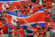 North Korean fans cheer their team before the start of the women's 1st round football match against Germany at the 2008 Beijing Olympic Games