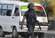 An East Timorese policeman wearing riot control gear, seen in Dili on July 16, a day after a protest that killed one man on the outskirts of the capital. About 64 vehicles, including five owned by police, were also damaged around Dili during the protests, according to police