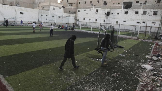 Free Syrian Army fighters walk with their weapons as fellow fighters play soccer at a recreation corner in Deir al-Zor