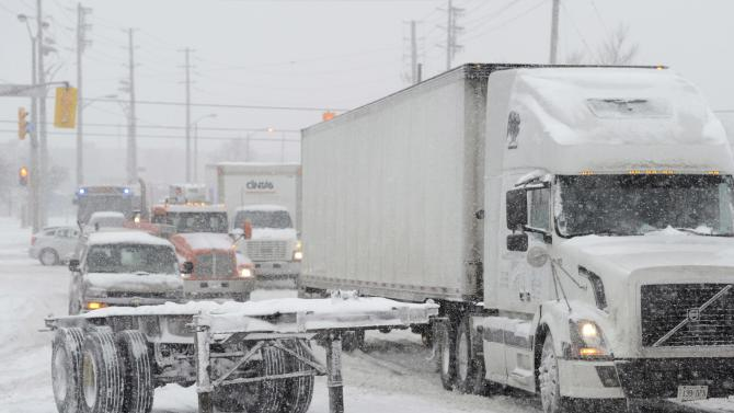 A truck tries to get past a trailer that was left by the side of the road during a snowstorm in Toronto on Friday, Feb. 8, 2013. A storm poised to dump up to 3 feet of snow from New York City to Boston and beyond beginning Friday could be one for the record books, forecasters warned, as residents scurried to stock up on food and water and road crews readied salt and sand. (AP Photo/The Canadian Press, Frank Gunn)