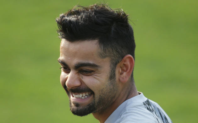 India's Virat Kohli laughs as he talks to his teammate during a training session ahead of their ICC Twenty20 Cricket World Cup match against Pakistan in Dhaka, Bangladesh, Thursday, March 20, 2014. (A