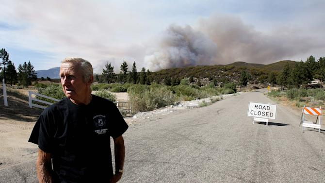 Dean Ness stands on Morris Ranch Rd. after he was ordered to evacuate from his home from the Mountain Fire near Lake Hemet on Tuesday July 16, 2013. The 14,200 acre forest fire near Idyllwild Calif., has caused Idyllwild and adjacent communities east of Highway 243 to issued mandatory evacuations for hundreds of homes Wednesday. (AP Photo/The Press-Enterprise, Frank Bellino)