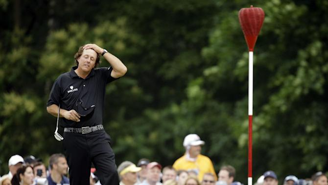 Phil Mickelson rubs his head before putting on the ninth hole during the fourth round of the U.S. Open golf tournament at Merion Golf Club, Sunday, June 16, 2013, in Ardmore, Pa. (AP Photo/Morry Gash)