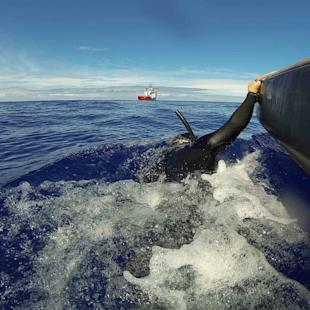 A fast response craft from Australian Defence Vessel Ocean Shield tows Able Seaman Clearance Diver Michael Arnold as he searches the ocean for debris of the missing Malaysian Airlines flight MH370