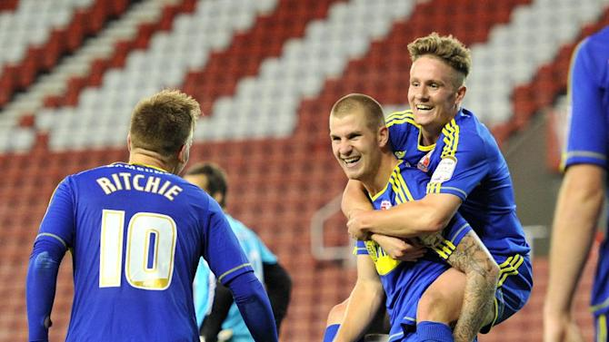 Swindon's James Collins, centre, celebrates scoring his third goal against Stoke