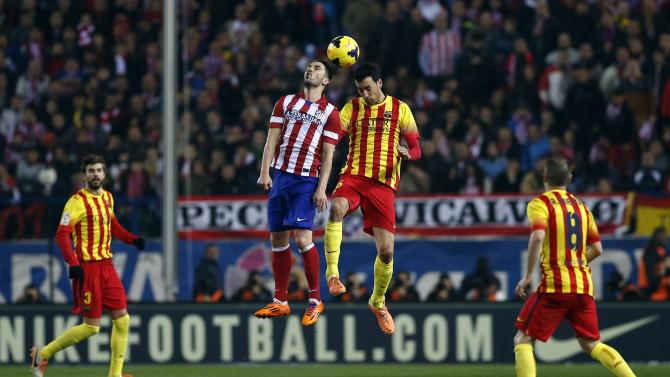 Barcelona's Sergio Busquets jumps for the ball with Atletico Madrid's David Villa during their Spanish first division soccer match at the Vicente Calderon stadium in Madrid