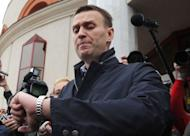 Russian opposition leader Alexei Navalny looks at his watch outside the court in the provincial northern city of Kirov, on April 17, 2013. Navalny has gone on trial on fraud charges he says were ordered by President Vladimir Putin to eliminate a top opponent, but the process is swiftly adjourned for a week to allow the defence more time to prepare for the trial