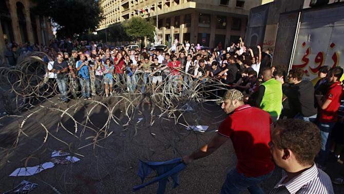 Civil society protesters try to remove barbed wire during a demonstration protesting the extension of parliament's mandate, near Parliament in Beirut, Lebanon, Friday, June 21, 2013. Lebanon's parliament on May 29 extended its term by a year and a half, skipping scheduled elections because of the country's deteriorating security linked to the civil war next door in Syria. (AP Photo/Bilal Hussein)