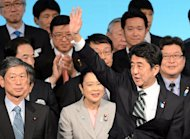 Japanese Prime Minister Shinzo Abe (R) waves at the party's annual convention in Tokyo on March 17, 2013. Abe said he hoped to meet the Chinese and South Korean leaders soon to improve relations strained by separate territorial rows