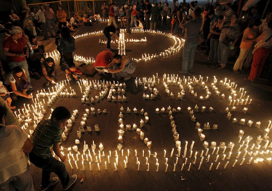People light candles during a vigil for those who they say died due to the lack of medical assistance, in Tegucigalpa