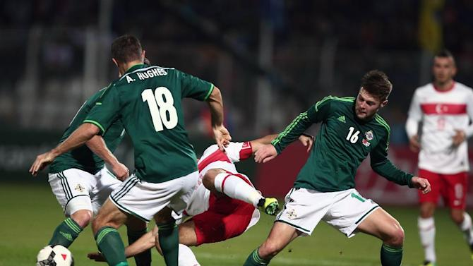 Northern Ireland's Aaron Hughes, left, and Oliver Norwood, right, fight for the ball against Turkish players during their friendly soccer match in Adana, Turkey,  Friday, Nov. 15, 2013.(AP Photo)