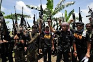 "A file photo of Ameril Umbrakato (3rd R-front), leader of the breakaway Muslim separatist group Bangsamoro Islamic Freedom Fighters (BIFF), holding a pistol and shouting ""Allah Akbar"" with his men on Mindanao. The BIFF launched simultaneous attacks across 11 towns in the southern Philippines on August 6, 2012"