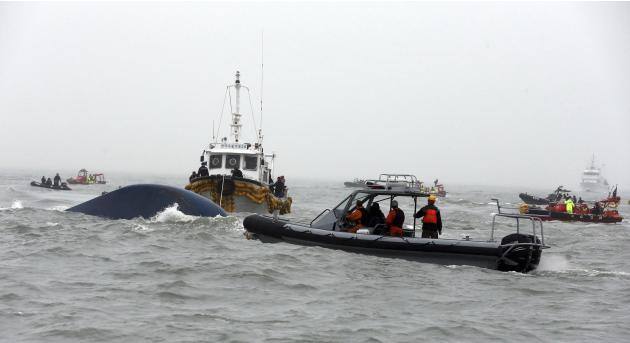 "South Korean rescue workers on a boat inject oxygen into the capsized passenger ship ""Sewol"" which sank in the sea off Jindo"
