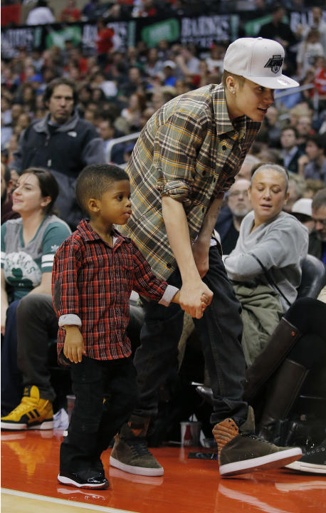 Canadian recording artist Justin Bieber walks with Christopher Emmanuel Paul II, the son of Los Angeles Clippers' Chris Paul, during the NBA basketball game between the Los Angeles Clippers and the Bo
