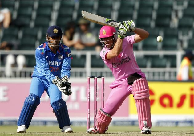 South Africa's captain de Villiers plays a shot as India's captain and wicketkeeper Dhoni looks on during their first ODI in Johannesburg