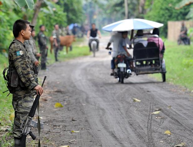 This file photo shows members of the southern Philippine rebel group, the Moro Islamic Liberation Front (MILF), lining a street as villagers pass by, in a town on Mindanao island, on September 19, 2009. The United States has warned Americans against travel to the southern Philippines just days after Australia and Canada issued similar advice