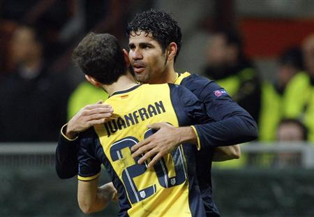 Atletico Madrid's Diego Costa (R) celebrates with teammate Juanfran after scoring against AC Milan during their Champions League round of 16 first leg soccer match at the San Siro stadium in Milan February 19, 2014. REUTERS/Alessandro Garofalo