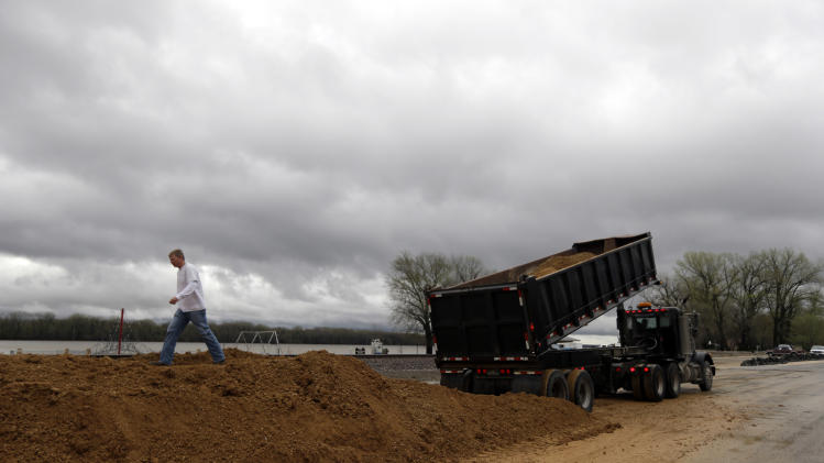 A man walks along a temporary levee being quickly constructed in hopes of holding back the rising Mississippi River Thursday, April 18, 2013, in Clarksville, Mo. Middle America was overwhelmed by weather Thursday, with snow in the north, tornadoes in the Plains, and torrential rains that caused floods and transportation woes. (AP Photo/Jeff Roberson)
